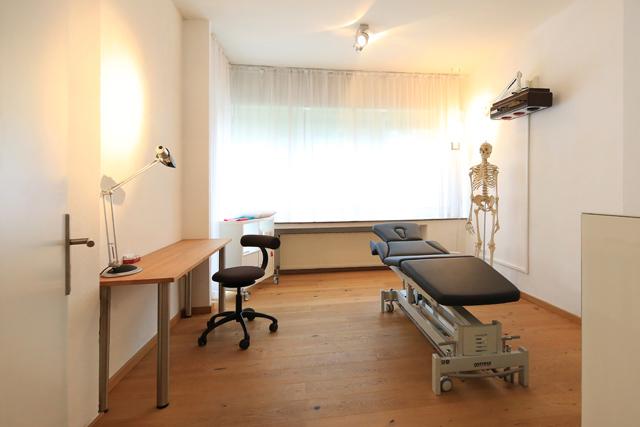 Praxisraum mit schwarzer Behandlungsbank und Skelett