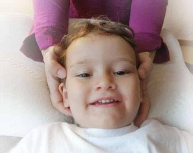 Zufriedenes Kind während einer Osteopathie Behandlung am kopf