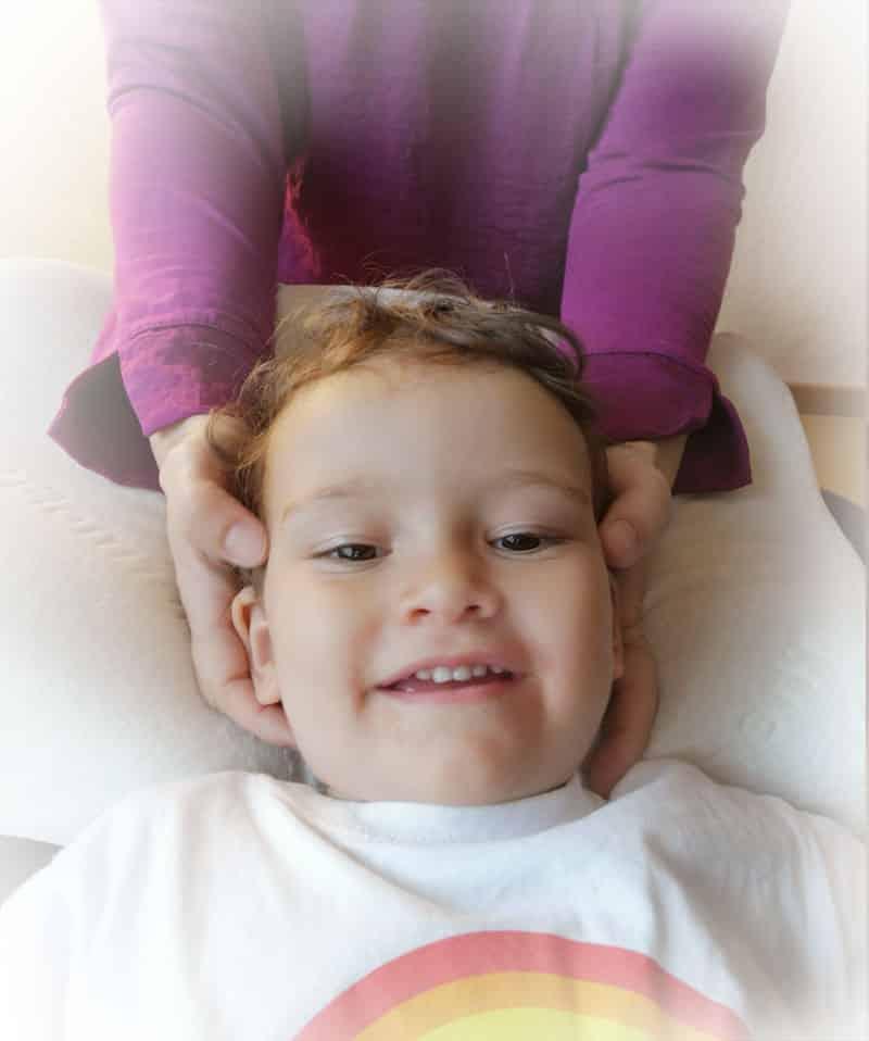 Craniosacrale Kinderosteopathie Behandlung am Kopf eines Kindes