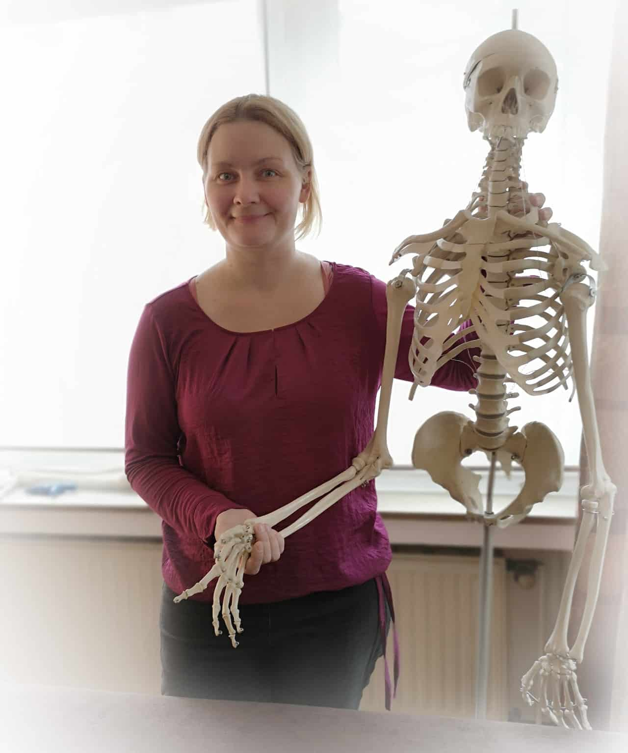 Osteopathin Petra Dorn neben einem Skelett in Osteopathie Köln